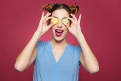 愉快的滑稽的少妇用橘子果酱糖果盖了她的眼睛 免版税图库摄影