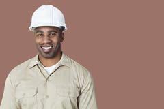 愉快的年轻建筑工人画象有安全帽的在棕色背景 库存图片