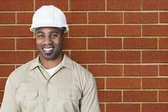 愉快的年轻建筑工人画象有安全帽的在砖墙 图库摄影