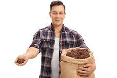 愉快的从粗麻布大袋的农夫提供的咖啡豆 库存图片