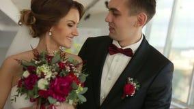 愉快的年轻英俊的爱恋看彼此的新郎和新娘 股票录像
