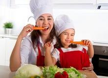 愉快的围裙和厨师帽子的吃红萝卜的母亲和小女儿在家一起有乐趣厨房 库存照片