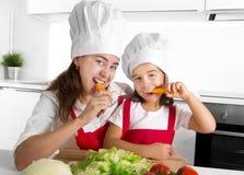 愉快的围裙和厨师帽子的吃红萝卜的母亲和小女儿在家一起有乐趣厨房 图库摄影