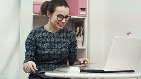 愉快的年轻设计师为有forein的顾客咨询并且提供新的衣裳与便携式计算机的网上会议 股票录像