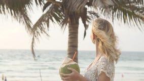 愉快的说谎海滩比基尼泳装妇女放松的饮用的新鲜的椰子的水下来晒日光浴乐趣加勒比假期 股票录像