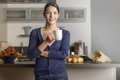 愉快的满足的主妇在她的厨房里 库存照片