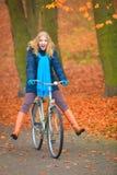 愉快的活跃妇女骑马自行车在秋天公园 免版税图库摄影