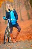 愉快的活跃妇女骑马自行车在秋天公园 库存图片