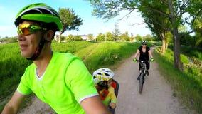 愉快的活跃家庭骑马自行车在绿园 股票录像