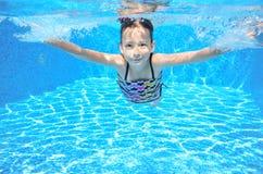 愉快的活跃水下的孩子在水池游泳 免版税图库摄影