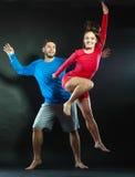 愉快的年轻跳跃为喜悦的夫妇男人和妇女 免版税库存照片