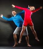 愉快的年轻跳跃为喜悦的夫妇男人和妇女 免版税库存图片