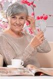 愉快的年迈的妇女饮用的咖啡 免版税图库摄影