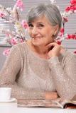 愉快的年迈的妇女饮用的咖啡 库存照片
