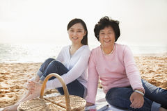 愉快的去野餐在海滩的祖母和孙女,看照相机 免版税库存图片