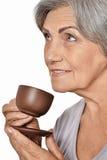 愉快的年长在白色backgro的妇女饮用的咖啡画象  库存照片