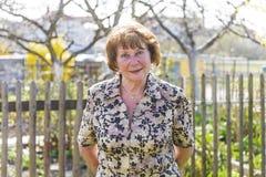 愉快的年长妇女站立感到骄傲在她的庭院里 免版税库存照片