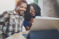 愉快的年轻非裔美国人的夫妇有网上录影闲谈一起通过触板在早晨在客厅 免版税库存照片