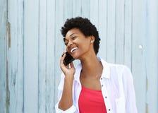 愉快的年轻非洲妇女谈话在手机 免版税图库摄影