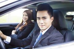 愉快的年轻驾驶在汽车的商人和妇女 免版税图库摄影