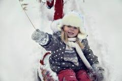 愉快的blondy孩子画象在使用在雪的冬天公园 库存图片