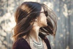 愉快的boho女孩画象获得乐趣和微笑在晴朗的街道的太阳镜的 时髦的摆在行家无忧无虑的女孩  免版税库存图片