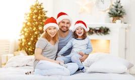 愉快的familymother父亲和孩子在圣诞节早晨在床上 免版税库存照片