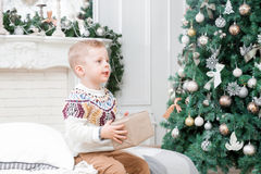 愉快的litle男孩在圣诞节早晨在家 在背景的圣诞树 新年好 库存图片