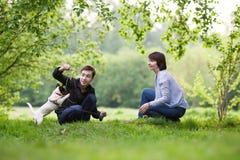 愉快的mather画象与儿子的和狗杰克罗素在夏天停放 免版税库存图片
