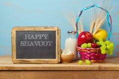 愉快的Shavuot问候设计用牛奶和水果篮在木土气桌上 免版税库存照片