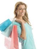 愉快的Shopaholic妇女运载的购物袋画象  免版税库存照片