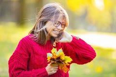 愉快秋天女孩微笑和快乐的举行的秋叶 有槭树的美丽的女孩在红色羊毛衫离开 库存照片