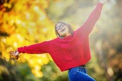 愉快秋天女孩微笑和快乐的举行的秋叶 有槭树的美丽的女孩在红色羊毛衫离开 免版税图库摄影