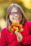 愉快秋天女孩微笑和快乐的举行的秋叶 有槭树的美丽的女孩在红色羊毛衫离开 库存图片