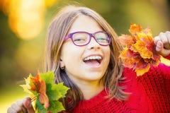愉快秋天女孩微笑和快乐的举行的秋叶 有槭树的美丽的女孩在红色羊毛衫离开 免版税库存图片