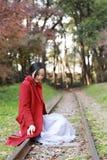 愉快秋天的妇女和极乐,美丽的妇女坐路轨在秋天公园 库存照片