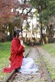 愉快秋天的妇女和极乐,美丽的妇女坐路轨在秋天公园 免版税库存图片