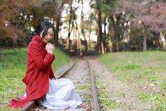 愉快秋天的妇女和极乐,美丽的妇女坐路轨在秋天公园 图库摄影