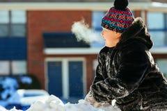 愉快笑的小女孩佩带的使用和跑在一个美丽的多雪的冬天公园 免版税库存图片