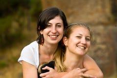 愉快美丽的女孩拥抱户外微笑 免版税库存图片