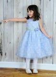 愉快美丽的蓝色礼服的女孩指向的一点 库存图片