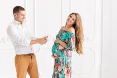 愉快美好的怀孕的夫妇一起期待孩子 男人和妇女白色minimalistic内部的 库存图片