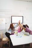 愉快董事给高五在会议在创造性的办公室 库存图片