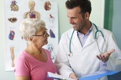 愉快血液的医生她的正常压前辈妇女 免版税库存照片