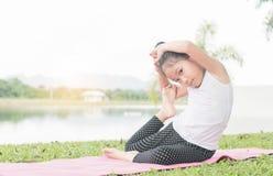 愉快逗人喜爱女孩使用体操在室外公园 免版税图库摄影
