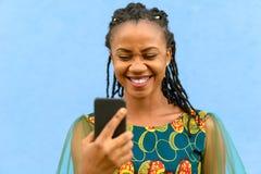 愉快逗人喜爱年轻非洲女孩读sms 图库摄影