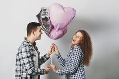 愉快逗人喜爱的快乐的卷曲的妇女从男孩接受心脏气球 免版税库存图片