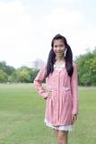 愉快青少年的美好的女孩礼服的桃红色和在公园放松 免版税库存照片