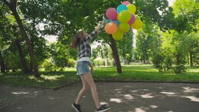愉快,嬉戏的女孩摆在与在步行的五颜六色的气球在晴朗的公园 股票录像