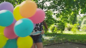 愉快,嬉戏的女孩摆在与在步行的五颜六色的气球在晴朗的公园 股票视频